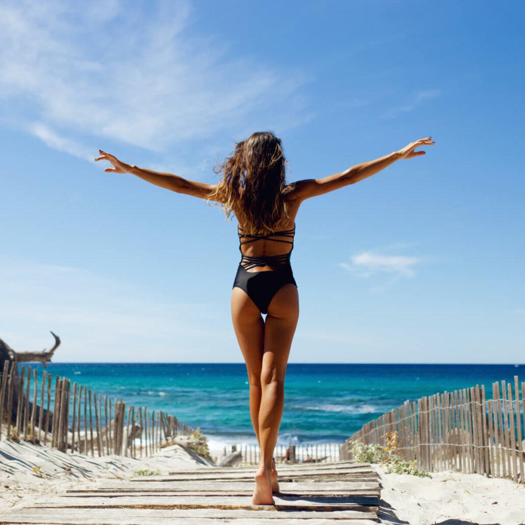 Frau in Rückansicht am Strand mit perfekter Bikiinifigur